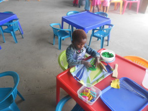 Likhona N deeply busy with her Playdough