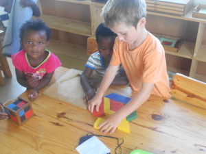 Josh helping Nomanesi with the Hexagon puzzle with Likhona J observing